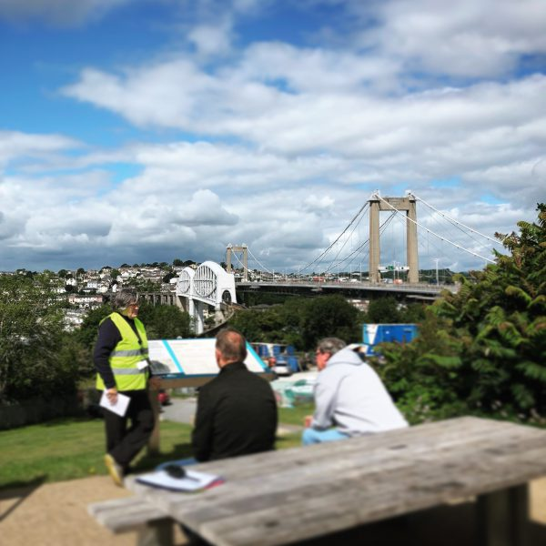 Woman in a high vis jacket gives a tour to two seated people with the bridges in the background.
